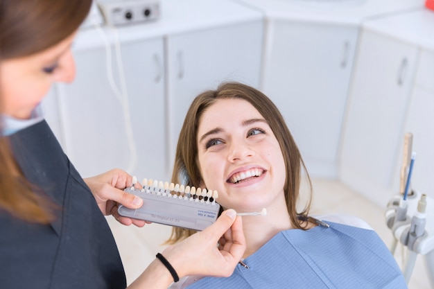 Femme dentiste avec des échantillons de couleur de dent choisissant la teinte pour la patiente