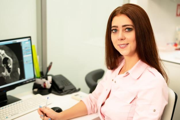Une femme dentiste est assise à une table, sur un ordinateur, un scanner de la mâchoire. le médecin est vêtu de vêtements professionnels.