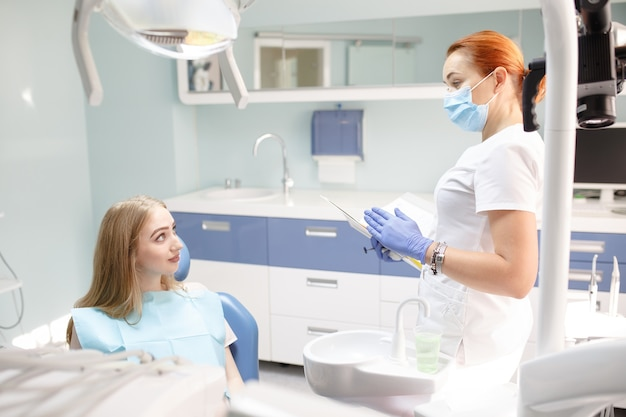Femme dentiste avec une femme patiente parlant au bureau de la clinique dentaire