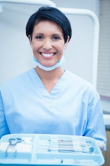 Femme dentiste en gommages bleus tenant un plateau d'outils