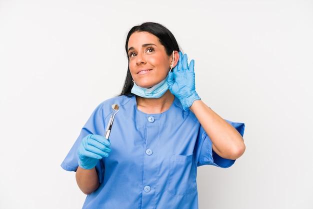Femme de dentiste isolée sur un mur blanc essayant d'écouter un potin.