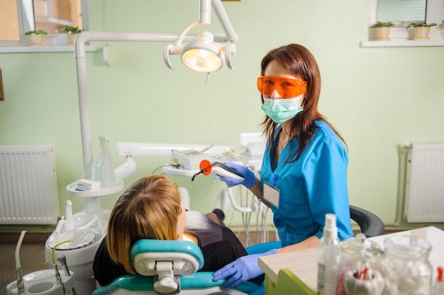 Femme dentiste avec lampe photopolymère de dentiste