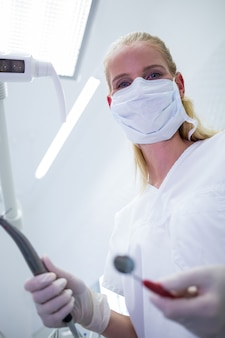 Femme dentiste avec masque chirurgical tenant des instruments dentaires