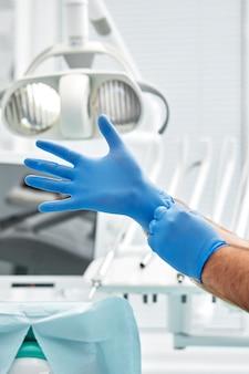Une femme dentiste met des gants sur fond de matériel dentaire dans un cabinet dentaire concept patient et dentiste heureux.
