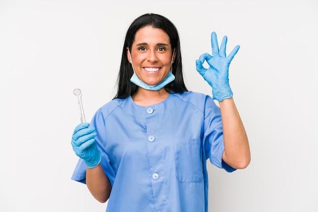 Femme dentiste sur mur blanc gai et confiant montrant le geste ok.