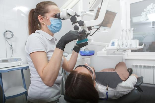 Femme dentiste opérant microscope dentaire, traitement des dents du patient