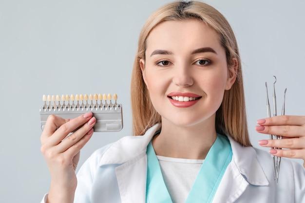 Femme dentiste avec des outils et des dents nuancier sur surface claire