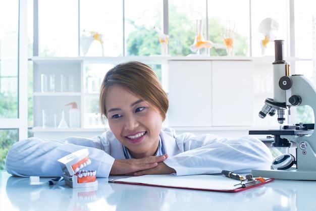 Femme dentiste sourire et regarder le modèle de dents.