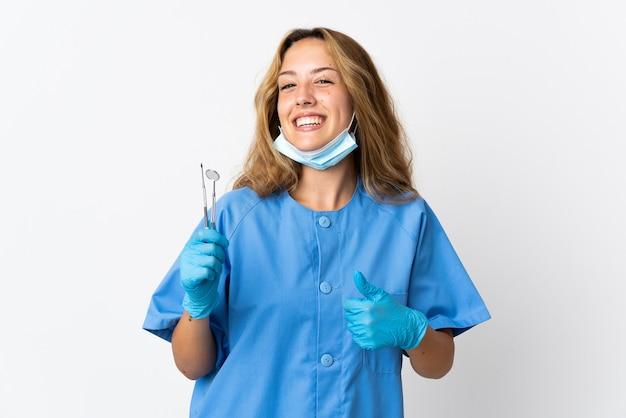 Femme dentiste tenant des outils isolés sur blanc donnant un geste de pouce en l'air