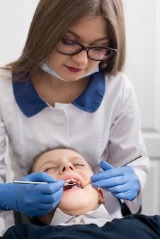Femme dentiste traite garçon dents l'étude