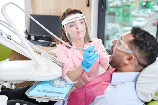Femme dentiste travaillant avec le patient
