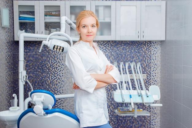 Une femme dentiste en uniforme blanc pose contre un appareil dentaire dans un cabinet dentaire