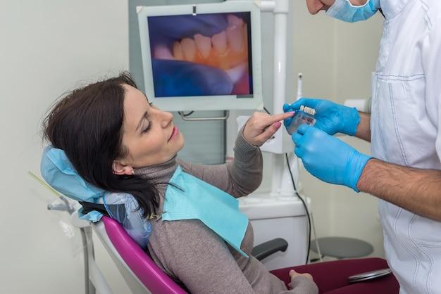 Femme en dentisterie pointant sur l'échantillonneur de dents