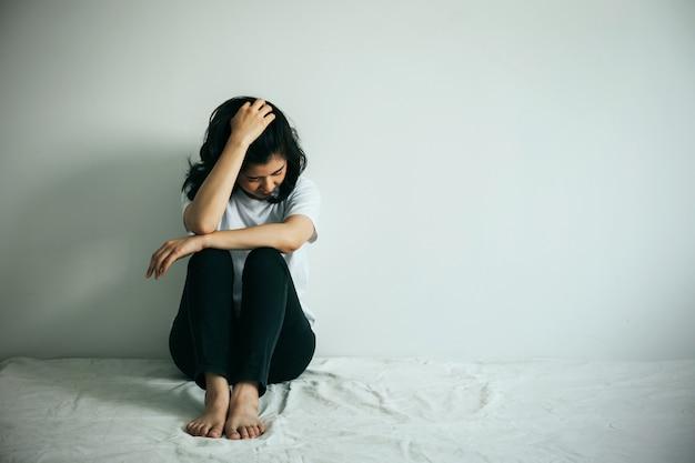La femme dépressive étreint son genou et pleure. femme triste assise seule dans une pièce vide.