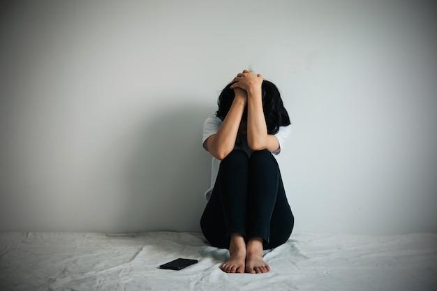 La femme dépressive étreint son genou et pleure. une femme triste était assise seule avec un téléphone à côté d'elle.