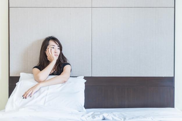 Femme déprimée assise sur le lit