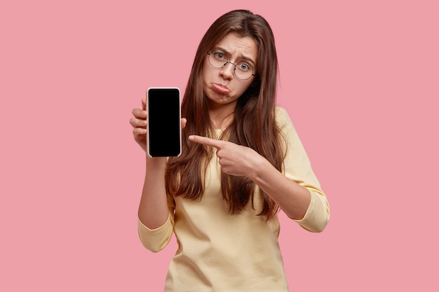 Une femme déprimée bouleversée porte sa lèvre inférieure, pointe sur un gadget moderne, montre un écran vide pour votre texte, n'aime pas comment cela fonctionne, porte des lunettes rondes