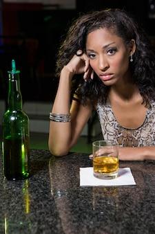 Femme déprimée buvant du whisky au comptoir du bar