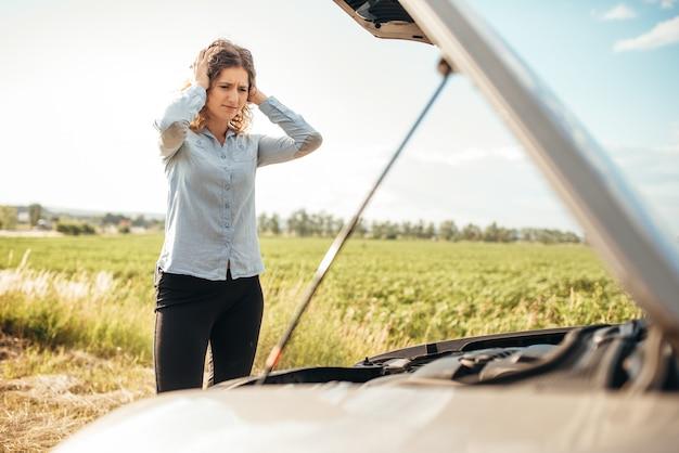 Femme déprimée regardant le moteur, voiture cassée