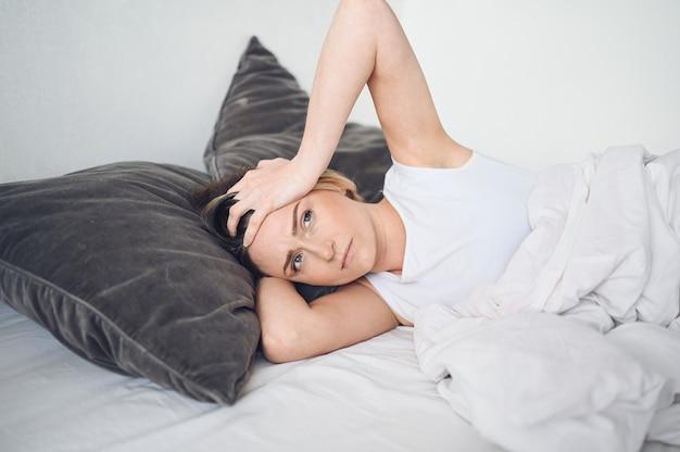 Femme déprimée tourmentée par un sommeil agité, elle est épuisée et souffre d'insomnie, de mauvais rêves ou de cauchemars, de problèmes psychologiques. lit ou matelas inconfortable et inconfortable. manque de sommeil