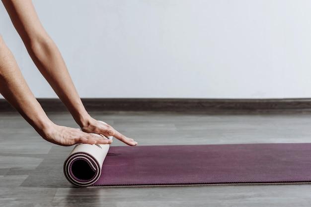 Femme déroulant un tapis de yoga sur fond blanc