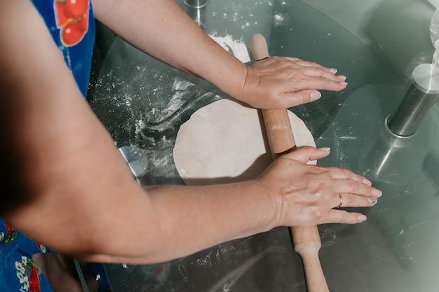 Une femme déroule la pâte sur la table
