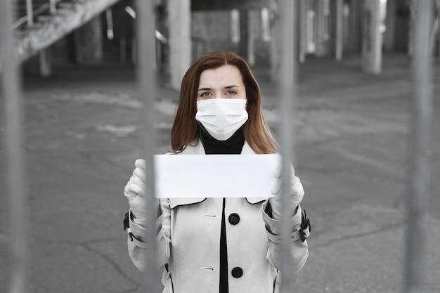 Femme derrière les barreaux en isolement tient une pancarte vide
