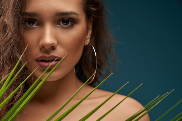 Femme derrière une feuille de palmier isolée sur bleu