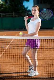 Femme derrière le filet de tennis tenant la balle de tennis