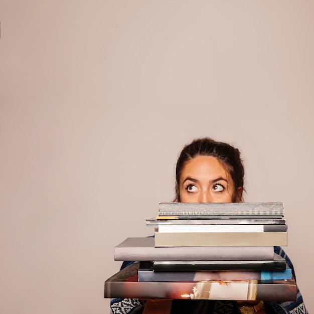 Femme derrière un tas de livres