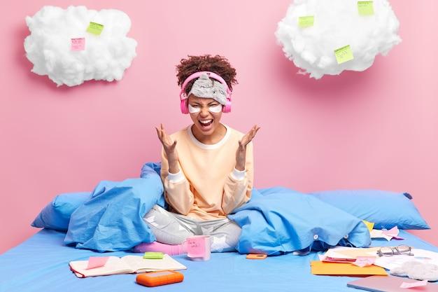 Une femme désespérée et ennuyée étant malade et fatiguée de la quarantaine et restant à la maison veut aller au travail pose sur un lit confortable occupé à préparer la tâche a un travail à distance