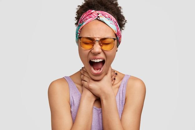 Femme désespérée à la peau sombre avec des cheveux foncés croquants, garde les mains sur le cou, crie nerveusement, étant fatiguée et stressée par quelque chose, porte des nuances à la mode, isolées sur un mur blanc. concept de suicide