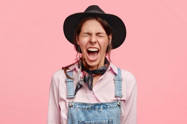 Une femme désespérée, propriétaire d'un ranch, hurle de désespoir, a des problèmes financiers, ne peut pas tout gérer seule, porte des vêtements de campagne, se tient contre un mur rose