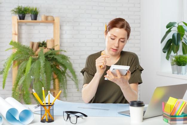 Femme designer au bureau travaillant sur un projet d'architectes