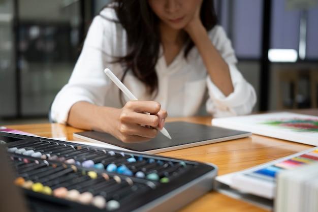Une femme designer recadrée tenant un stylet et dessinant sur une tablette numérique.