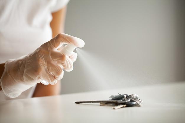 Femme désinfectant les clés avec un désinfectant sur la table