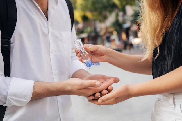 Femme désinfectant les mains de son mari