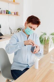 Femme désinfectant son smartphone à la maison