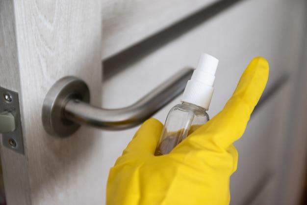 Une femme désinfecte et nettoie la poignée de porte avec un désinfectant en spray antibactérien pour se protéger contre les virus, les germes