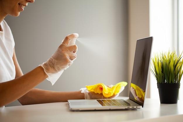 Femme désinfecter l'ordinateur portable avec des lingettes humides et un antiseptique