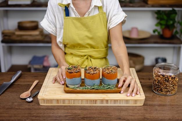 Femme avec des desserts sucrés sains colorés puddings de chia au lait d'amande, extrait de spiruline bleue, graines de chia, confiture de mangue pappaya et granola maison. sur la table en bois dans la cuisine à la maison.