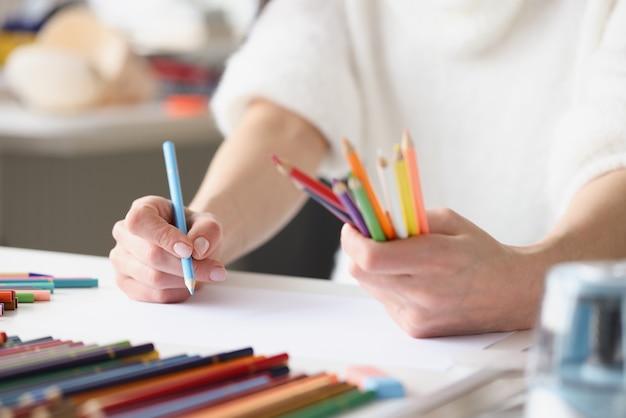 Femme dessin avec des crayons multicolores sur une feuille de papier blanche en gros plan
