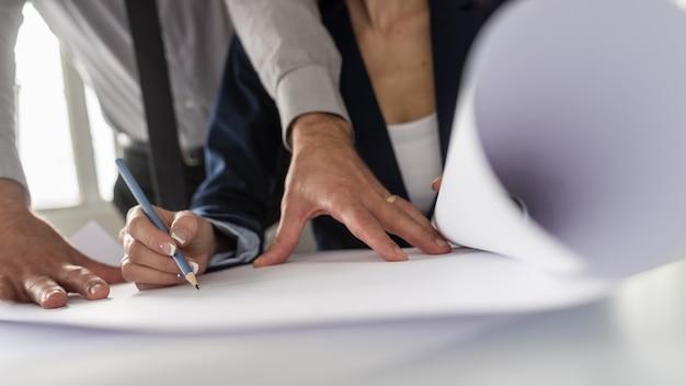 Une femme dessinant au crayon alors que son partenaire ou associé se tient au-dessus d'elle dans une vue en contre-plongée.