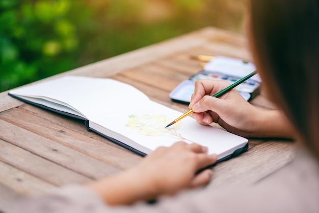 Une femme dessinant et peignant une image d'arbre avec l'aquarelle