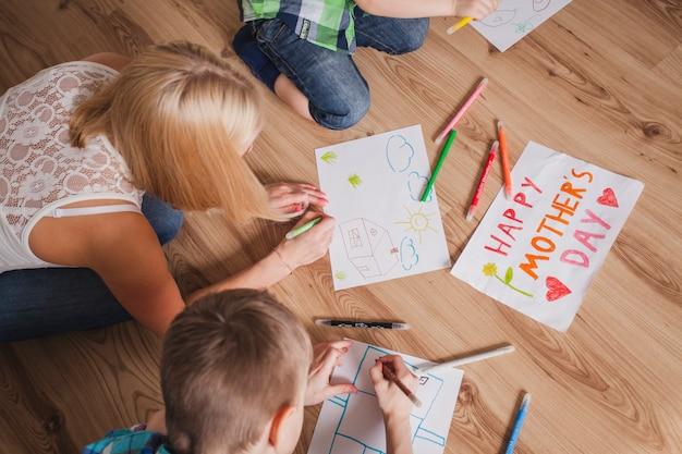 Femme dessinant avec ses enfants pour la fête des mères