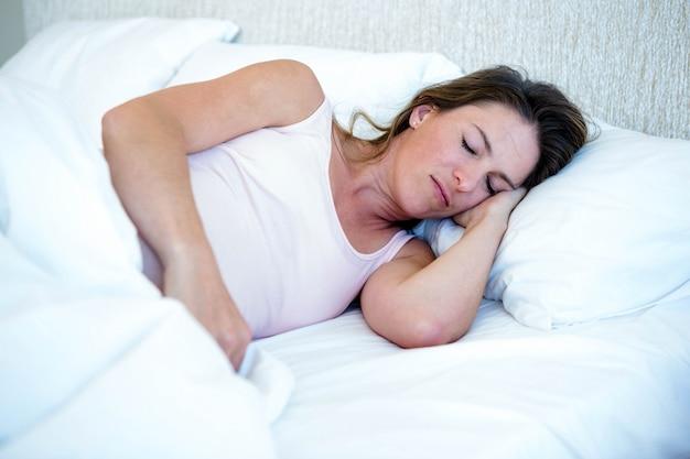 Femme détendue allongée dans son lit, endormie