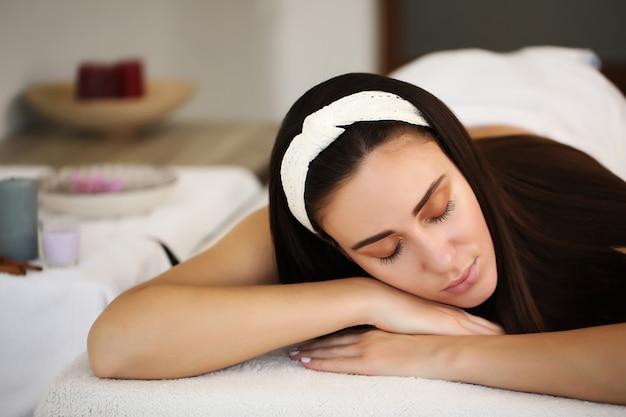 Femme détendue couchée dans un salon spa avec les yeux fermés, en attente de massage