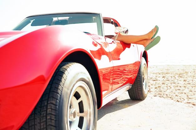 Femme détendue jambes dans une fenêtre de voiture sur la plage