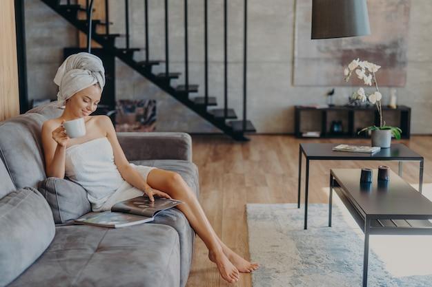 Femme détendue avec des jambes minces aime boire du thé est assis sur un canapé confortable enveloppé dans une serviette de bain