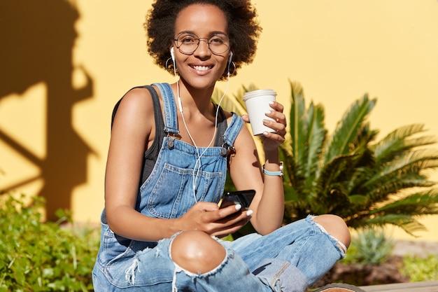 Une femme détendue à la peau sombre ressent le bonheur pendant qu'elle rêve, tient un café à emporter et un smartphone dans ses mains, connectée à des écouteurs, écoute de la musique agréable dans les écouteurs, porte une salopette en lambeaux, des lunettes